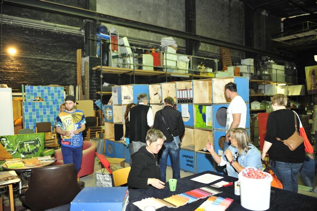 Blick in die Ausstellung: Workshop-Tisch im Vordergrund und Ausstellungswürfel (Hintergrund).