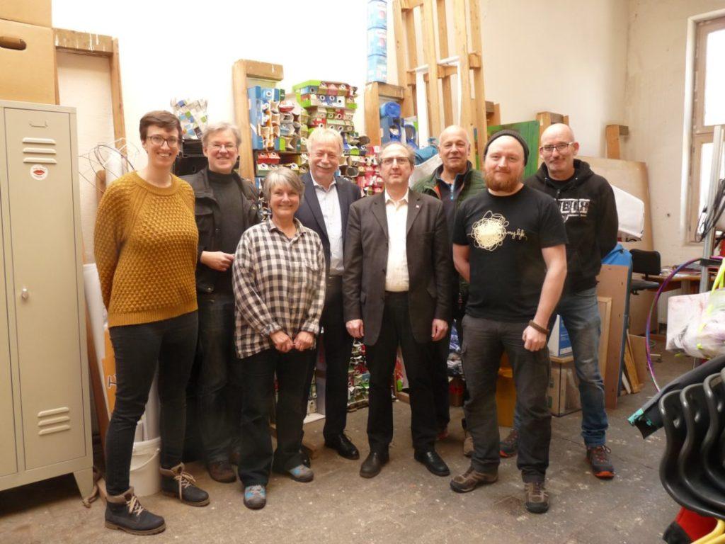 Gruppenbild in der Werkstatt, Hintergrund: zahlreiche gestapelte Getränkeverpackungen.