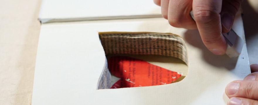 weißes Buchseiten mit ausgestanztem Innenraum, in dem ein rotes Herz aus Papier liegt.